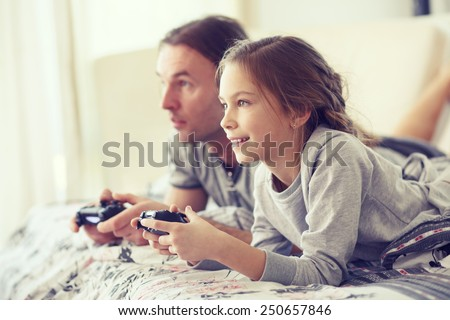Child playing video game on tv with father in morning at bed at home - stock photo