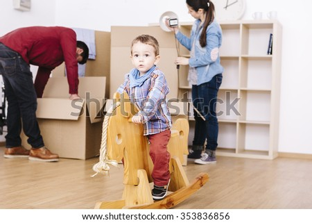 Child playing with a wooden horse while parents make moving - stock photo