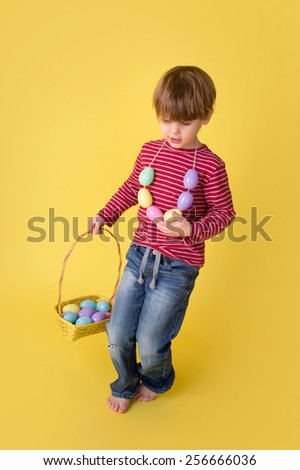 Child playing with an easter egg necklace and basket, easter egg hunt concept.