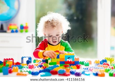 Child playing with colorful toys sitting at a window. Little curly boy with educational toy blocks. Children play at day care or preschool. Mess in kids room. Toddlers build a tower in kindergarten. - stock photo