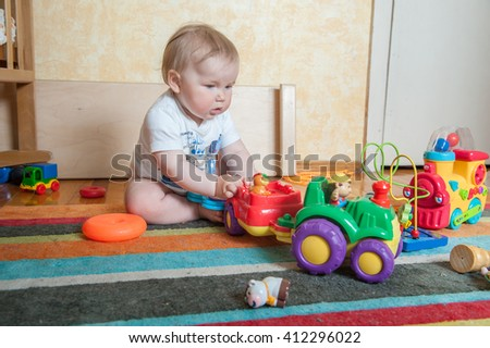 Child playing with educational toys. cute baby girl  boy, playing with toy train, blocks, tracktor, building towers at home or day care. Educational child toys. preschool and kindergarten. - stock photo