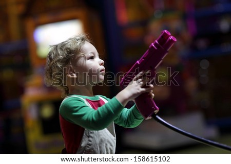 Child playing with pistol at indoor playground - stock photo