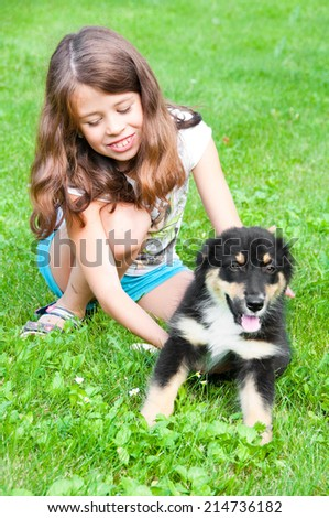 Child playing with puppy of australian shepherd outdoors - stock photo