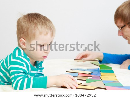 child playing with puzzle, early education concept - stock photo