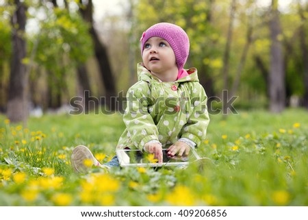 Child playing with tablet outdoors. Cheerful child with a portable PC in your hands.