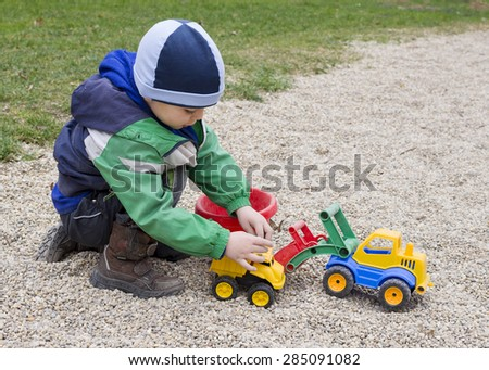 Child playing with toy digger and car in stones pebbles at playground park.