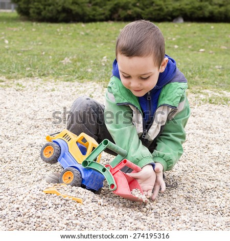 Child playing with toy digger and stones pebbles in playground park. - stock photo