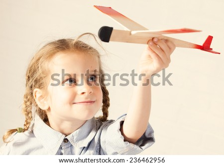 Child playing with toy. Girl with plane - stock photo