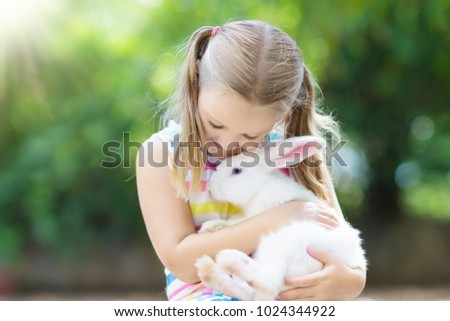 Child playing with white rabbit. Little girl feeding and petting white bunny. Easter celebration. Egg hunt with kid and pet animal. Children and animals. Kids take care of pets. Spring Easter garden.