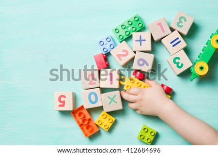 Child playing with wooden cubes with numbers and colorful toy bricks on a turquoise wooden background. Toddler learning numbers. Hand of a child taking toys. - stock photo