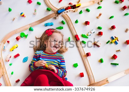 Child playing with wooden train, rails and cars. Toy railroad for kids. Educational toys for preschool and kindergarten children. Little girl at daycare. View from above, kid playing on the floor. - stock photo