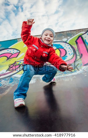 child plays on a hill painted graffiti