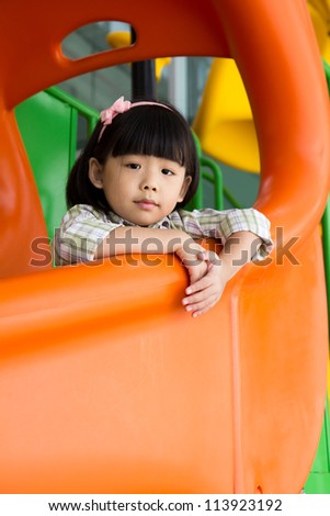 Child plays on slide at an indoor playground - stock photo