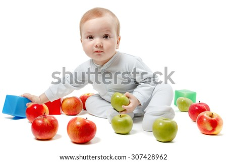 Child plays with apples and toys. Studio Portrait, isolated on a white background - stock photo