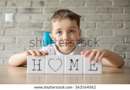 """Child plays with cubes and puts it together in word """"home"""". Dressed in a white polo shirt  - stock photo"""