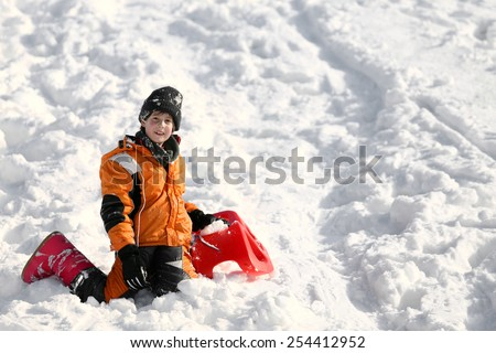 Child plays with sled in the snow in winter in the mountains