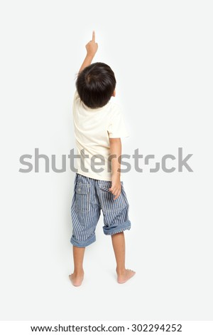 child pointing at wall. Back view. Isolated on white background - stock photo