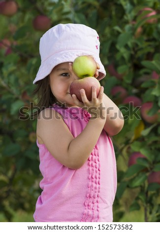 Child posing with 2 apples stacked above each other.