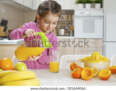 Child pouring fresh made orange juice ready for drinking - stock photo