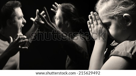 Child prays for peace in the family on the background of quarreling parents. MANY OTHER PHOTOS FROM THIS SERIES IN MY PORTFOLIO.  - stock photo