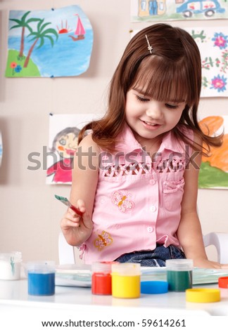 Child preschooler painting in classroom. Child care. - stock photo
