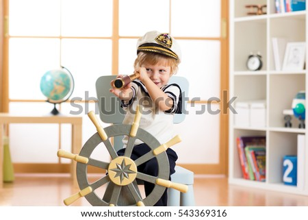 Child pretend to be sailor. Little boy looking through spy glass playing at home.