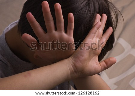 Child raising hands to protect itself - stock photo