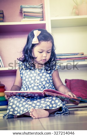 Child read, cute little girl reading a book and sitting on floor,vintage filter - stock photo