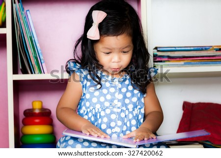 Child read, cute little girl reading a book on bookshelf background - stock photo