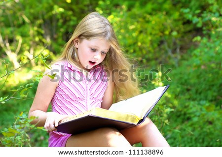 Child reading a book in the park - stock photo