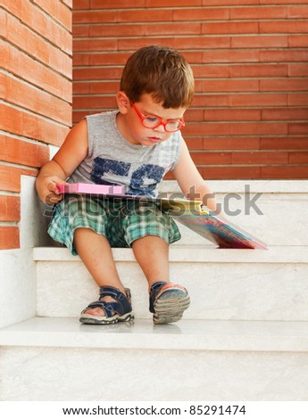Child reading a book sitting on the stairs - stock photo
