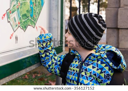 Child reading public map or plan of city park on a board - stock photo