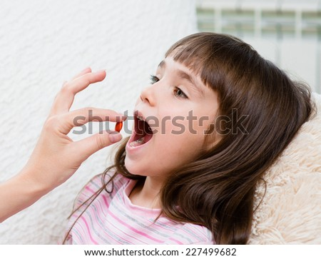 Child receiving pill - closeup - stock photo