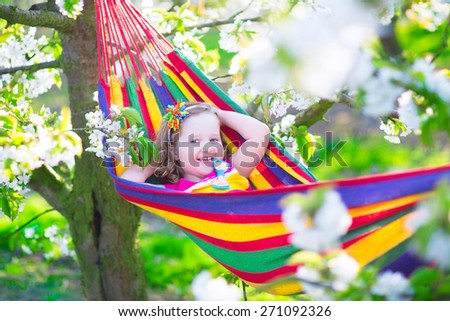 Child relaxing in hammock. Cute little toddler girl playing in a blooming cherry garden with white flowers. Kids having fun during spring vacation on a farm with fruit tree orchard. Kids gardening. - stock photo