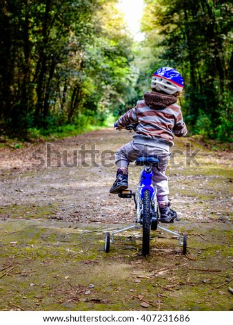 child riding a bicycle in the woods. Vertical - stock photo