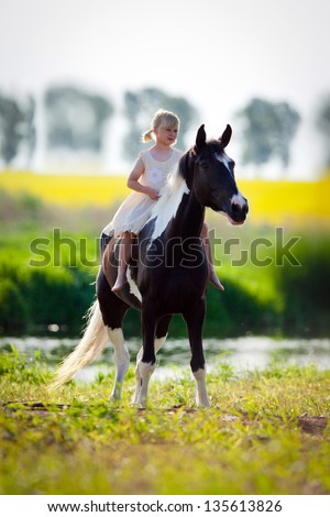 Child riding a horse in meadow in spring. - stock photo