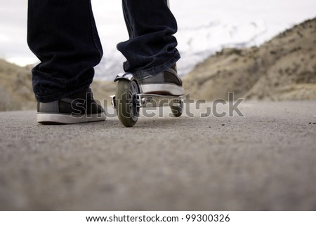 child riding scooter on paved pathway with mountains in background - stock photo