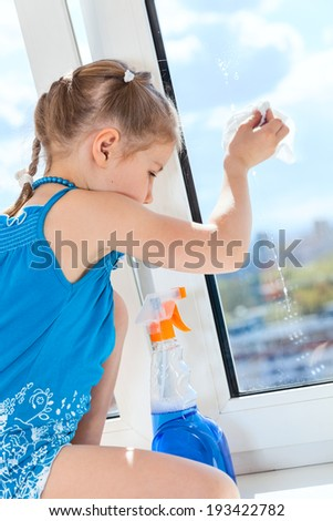 Child rubbing glass plastic window with a detergent