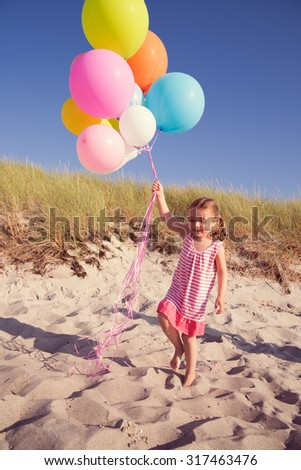 child runnig beach with colorful baloons - stock photo