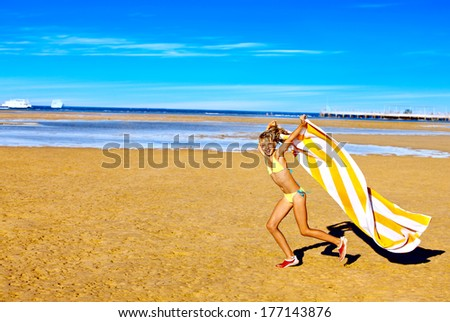 Child running at beach with towel. Summer outdoor.