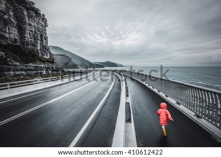 Child running on Sea Cliff Bridge, Grand Pacific Drive, Sydney, Australia. Black and white image with selective coloring. - stock photo