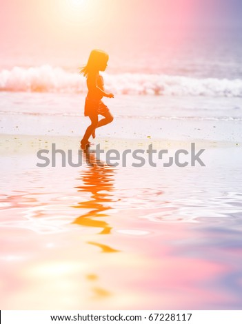 Child running on water at ocean beach at sunset. - stock photo