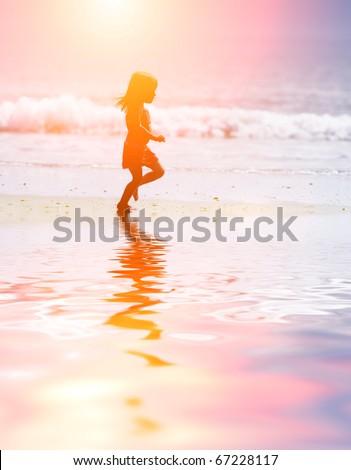 Child running on water at ocean beach at sunset. - stock photo