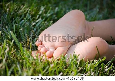 Child's bare feet in green grass - stock photo