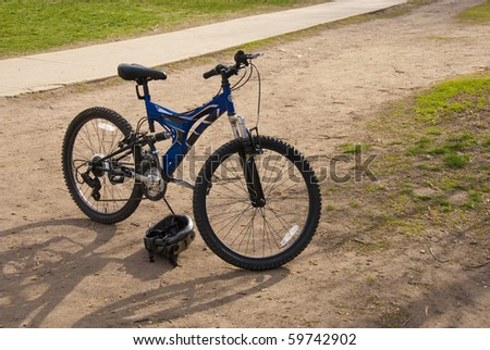 Child's bicycle and helmet standing ready to go on a dirt field by a bike path. - stock photo