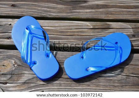 Child's blue flip flops sitting on a boardwalk - stock photo
