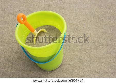 Child's bucket of sand and shovel at the beach - stock photo