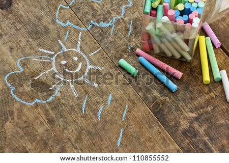 Child's drawings and colored chalk on wooden background - stock photo
