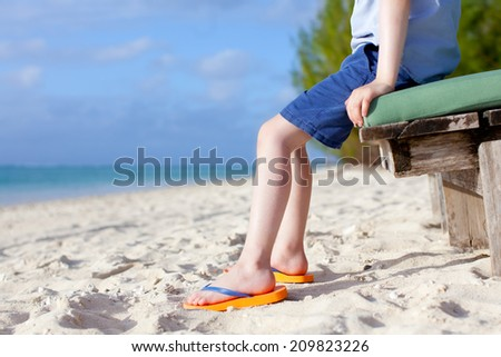 child's feet at the tropical beach - stock photo