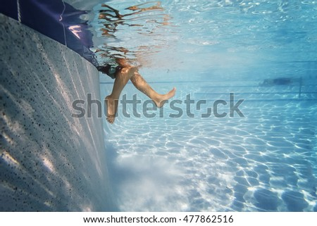 Child's feet in water on side of pool